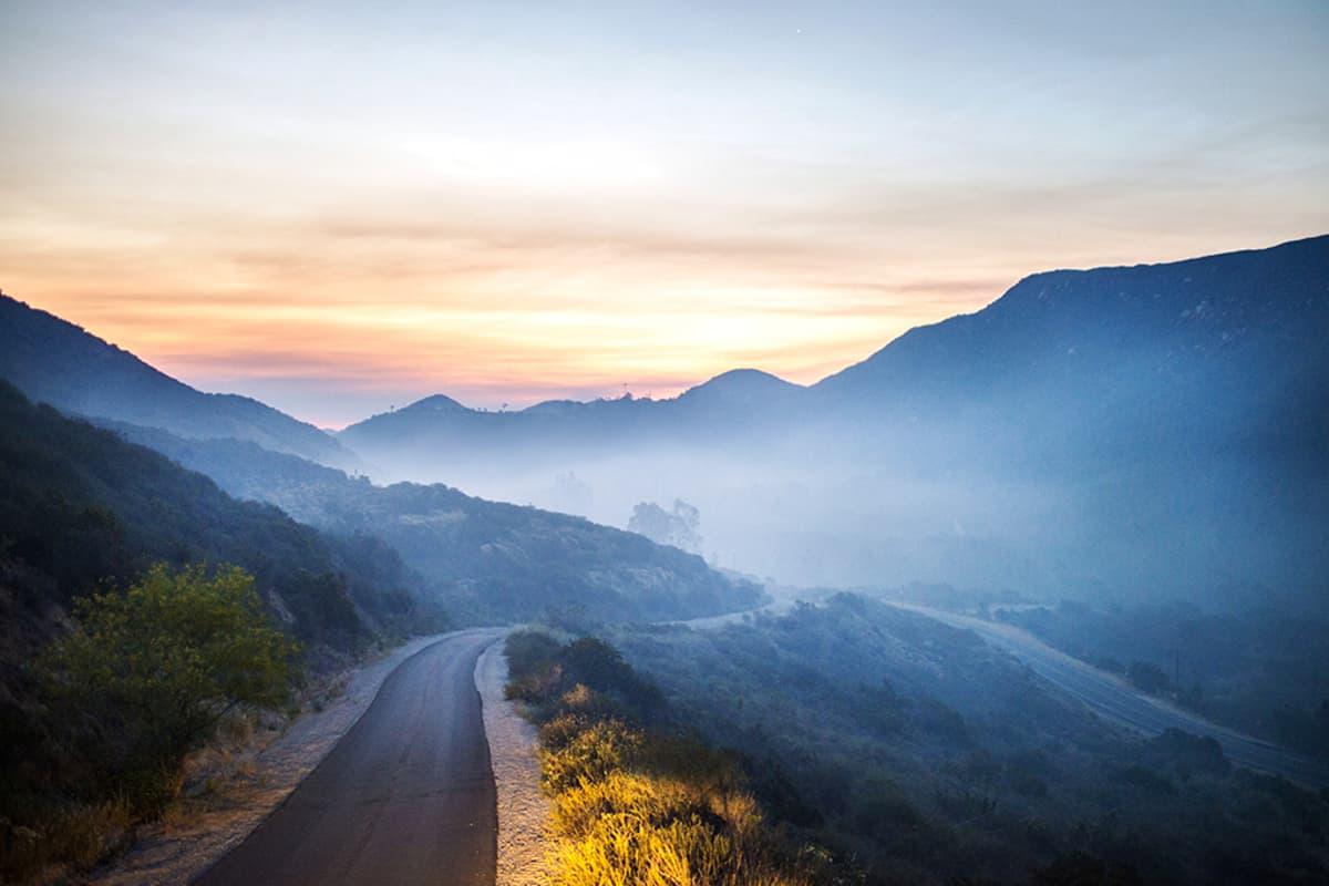 Maantie joka katoaa metsäpalon savuihin.