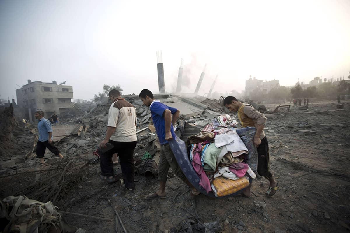 Palestiinalaiset keräsivät tavaroitaan Israelin ilmaiskussa tuhotuista kodeistaan Gazassa 8. heinäkuuta 2014.
