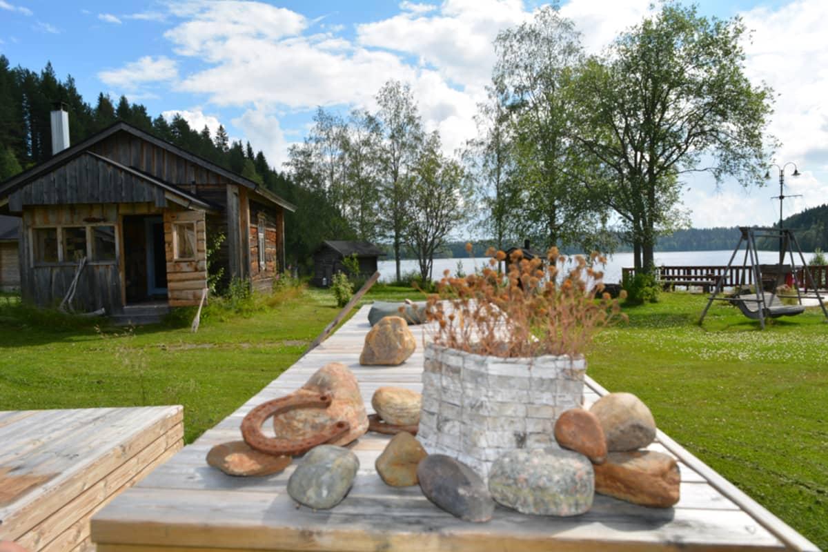 Kantturan pihan vanhalla pöydällä on kauniisti aseteltuna tuohikori, jossa on kukkia, kiviä ja ruosteisia hevosenkenkiä.