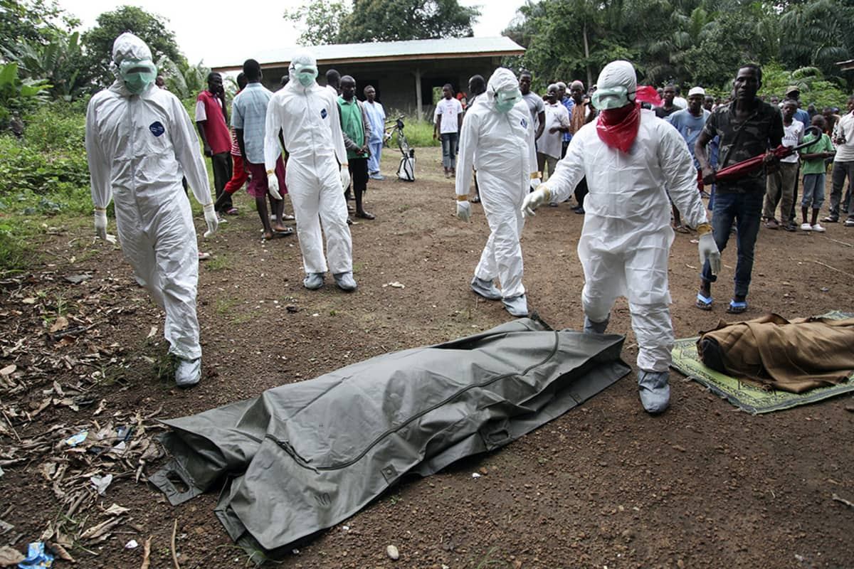 Liberialaiset terveystyöntekijät valmistelevat Ebola-virukseen kuolleiden hautausta Monrovian lähistöllä 6. elokuuta 2014.