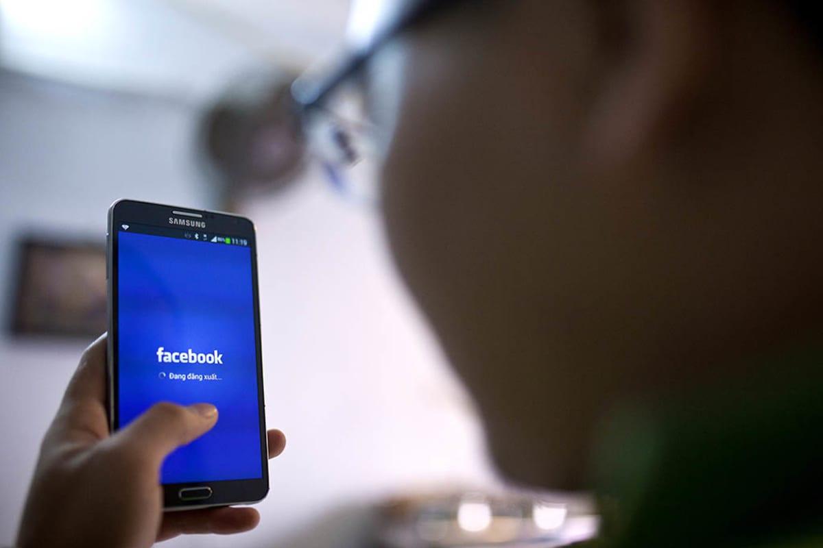 Henkilö käyttää facebook-sovellusta älypuhelimella.