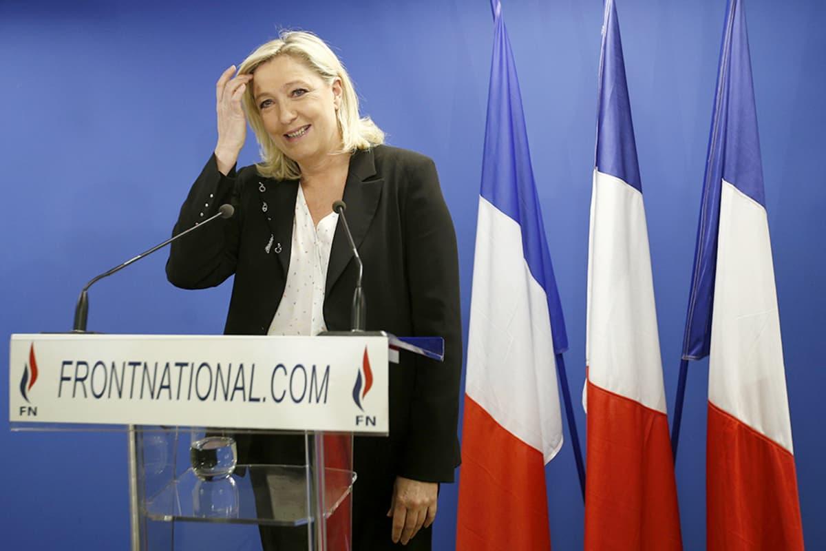 Marine Le Pen puhujakorokkeella ja kolme Ranskan lippua