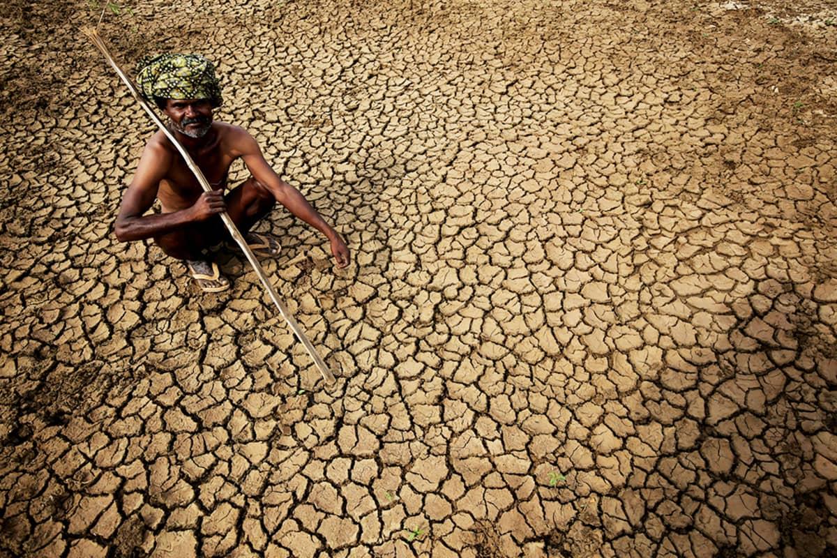 Maanviljelijä istuu kuivuneen maansa äärellä.