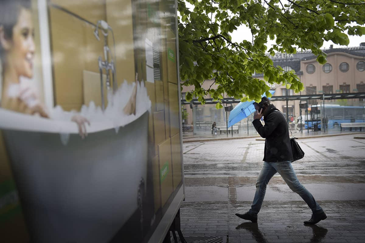 Mies kävelee tuulessa sateenvarjon kanssa