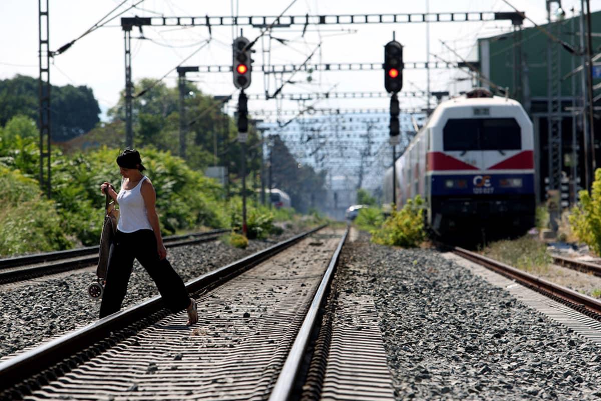 Nainen käveli junaradan yli julkisen sektorin lakon takiaThessalonikissa keskiviikkona.