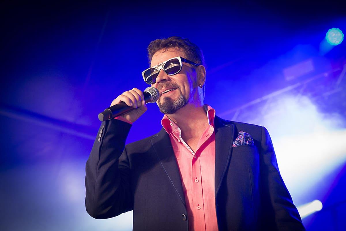 Pate Mustajärvi esiintyi Iskelmä-Finlandian julkistustilaisuudessa, vahvasti sinisävyinen tausta takanaan.