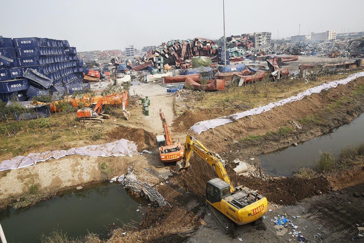 Pelastustyöntekijät rakentavat esteitä hillitäkseen myrkyllisten aineiden valumia.