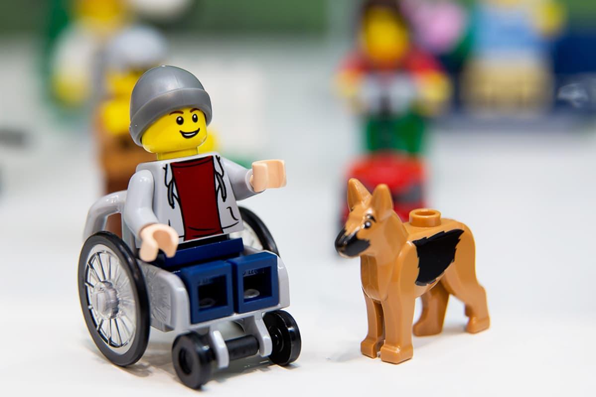 Pyörätuolissa istuva Lego-hahmo avustajakoiran seurassa.