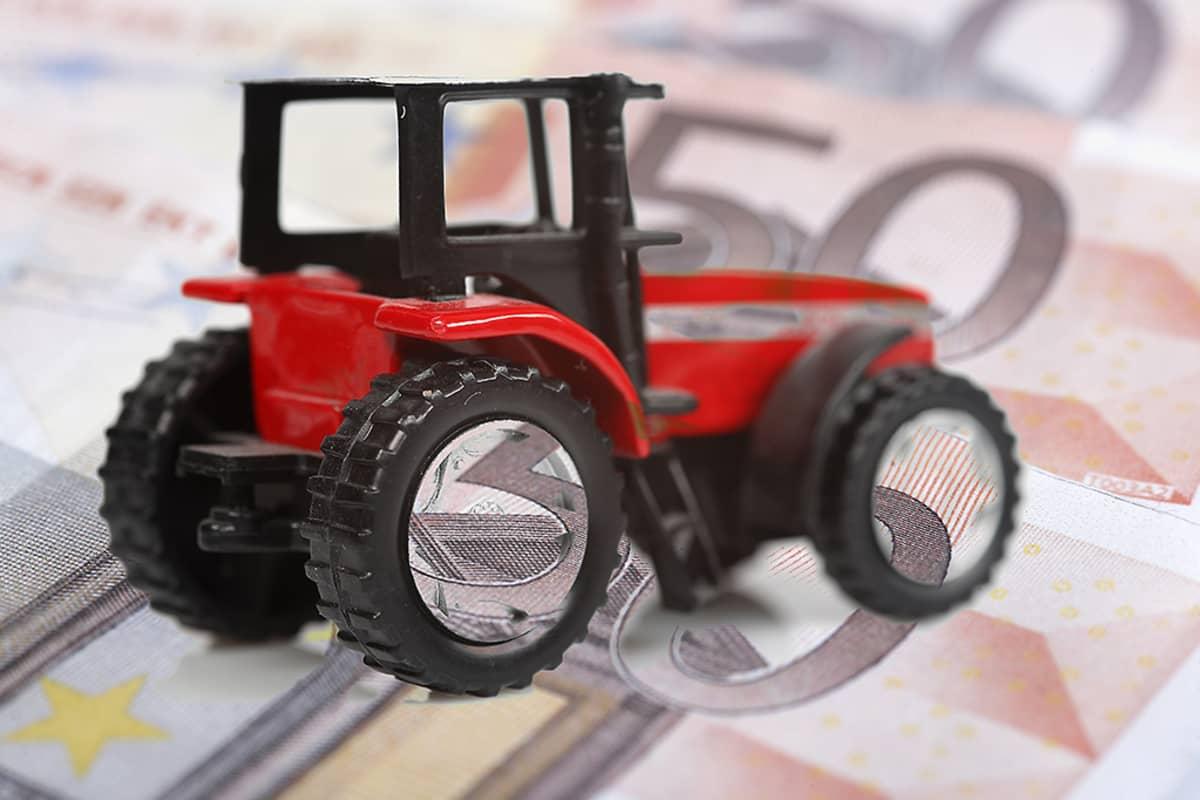 Punainen leikkitraktori viidenkymmenen euron setelien päällä.