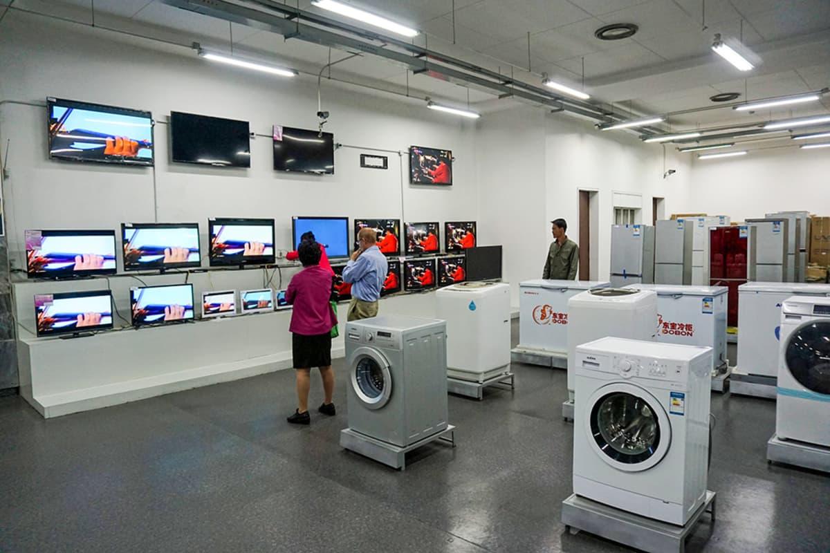televisioita ja pesukoneita myymälässä