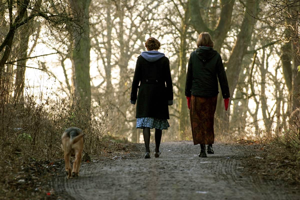 kaksi naista ja koira kävelyllä puistossa