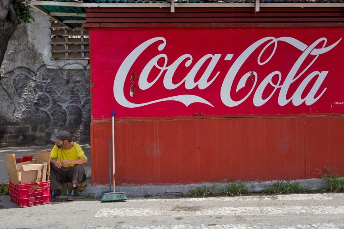 Mies istuu Coca Cola -kioskin vieressä Caracasissa, Venezuelassa 2016. Miehen vieressä on lakaisuharja ja muovilaatikossa pahvia.