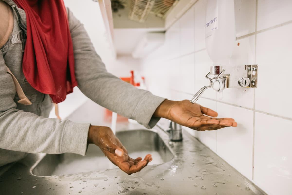 Nuori henkilö pesee käsiään.