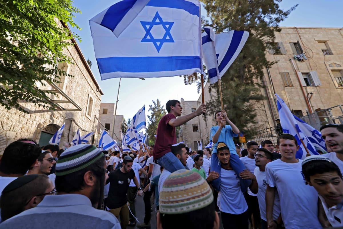 Israelilaisjoukko heiluttaa Israelin lippuja.