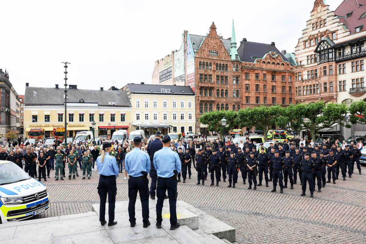 Joukko poliiseja seisoo aukiolla.