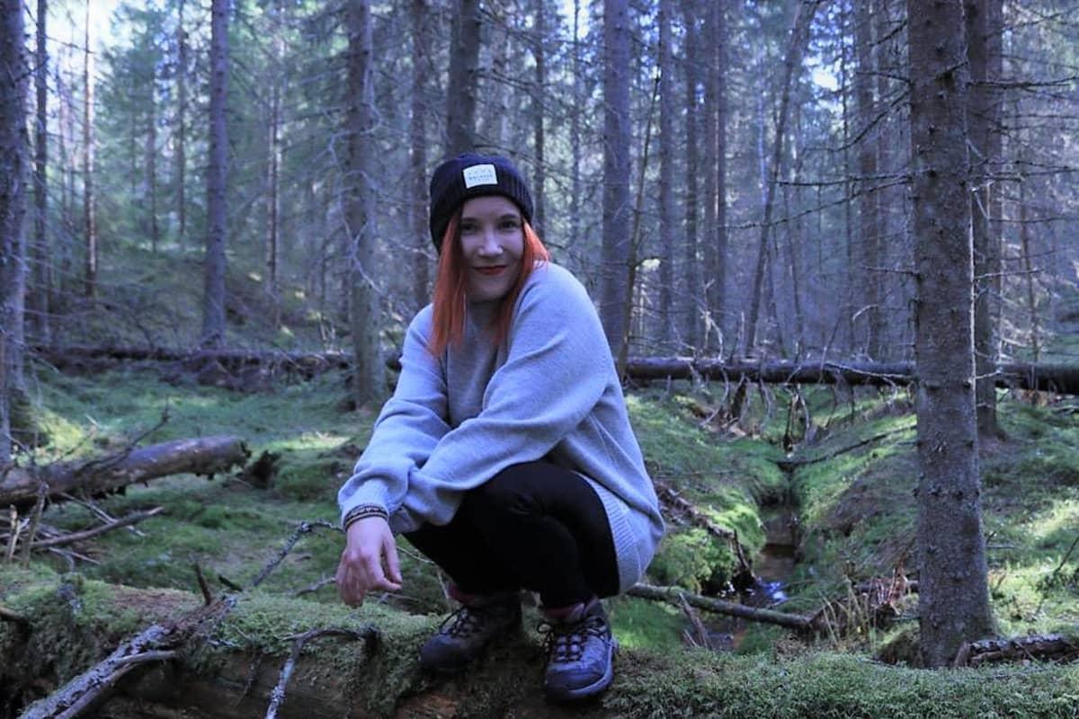 Johanna Rita istuu metsässä kannon päällä