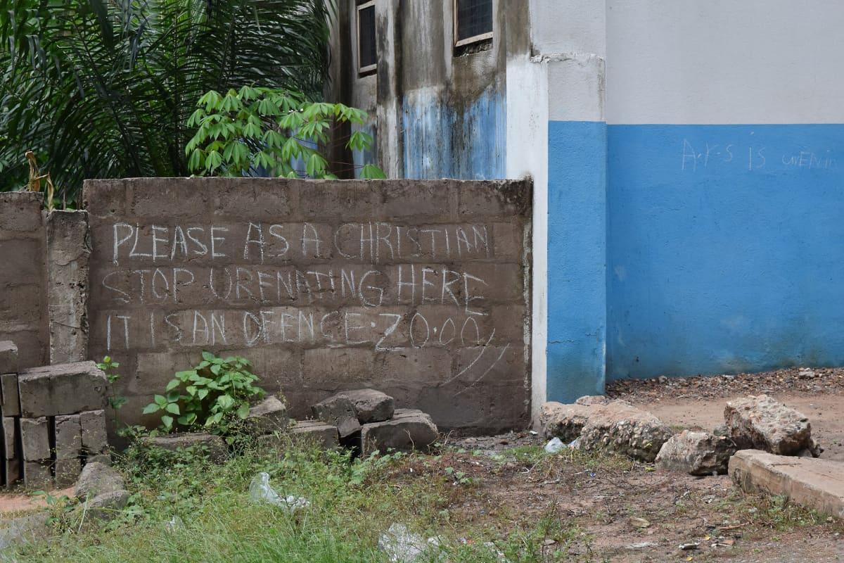 Kirjoitus betoniaidassa pyytää, ettei aidan viereen virtsattaisi.