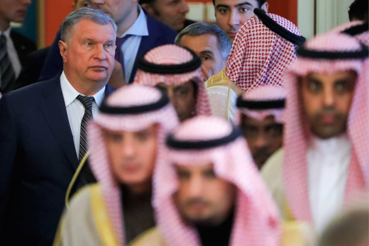 Igor Setshin seisoo tummassa puvussa kuvan vasemmassa reunassa. Etualalla kulkee joukko saudeja perinteisissä asuissaan.