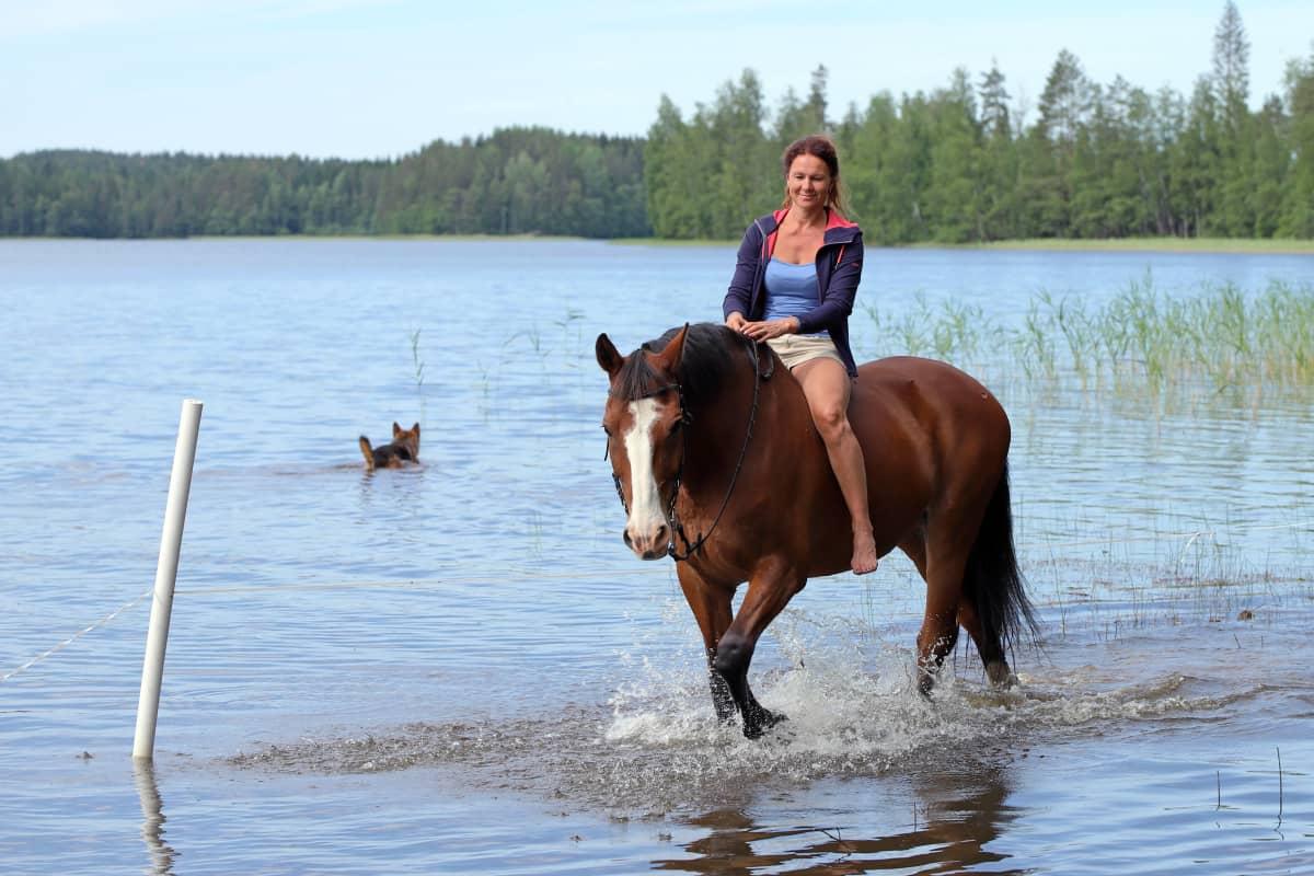 Melina Holmberg ratsastaa hevosella rantavedessä.