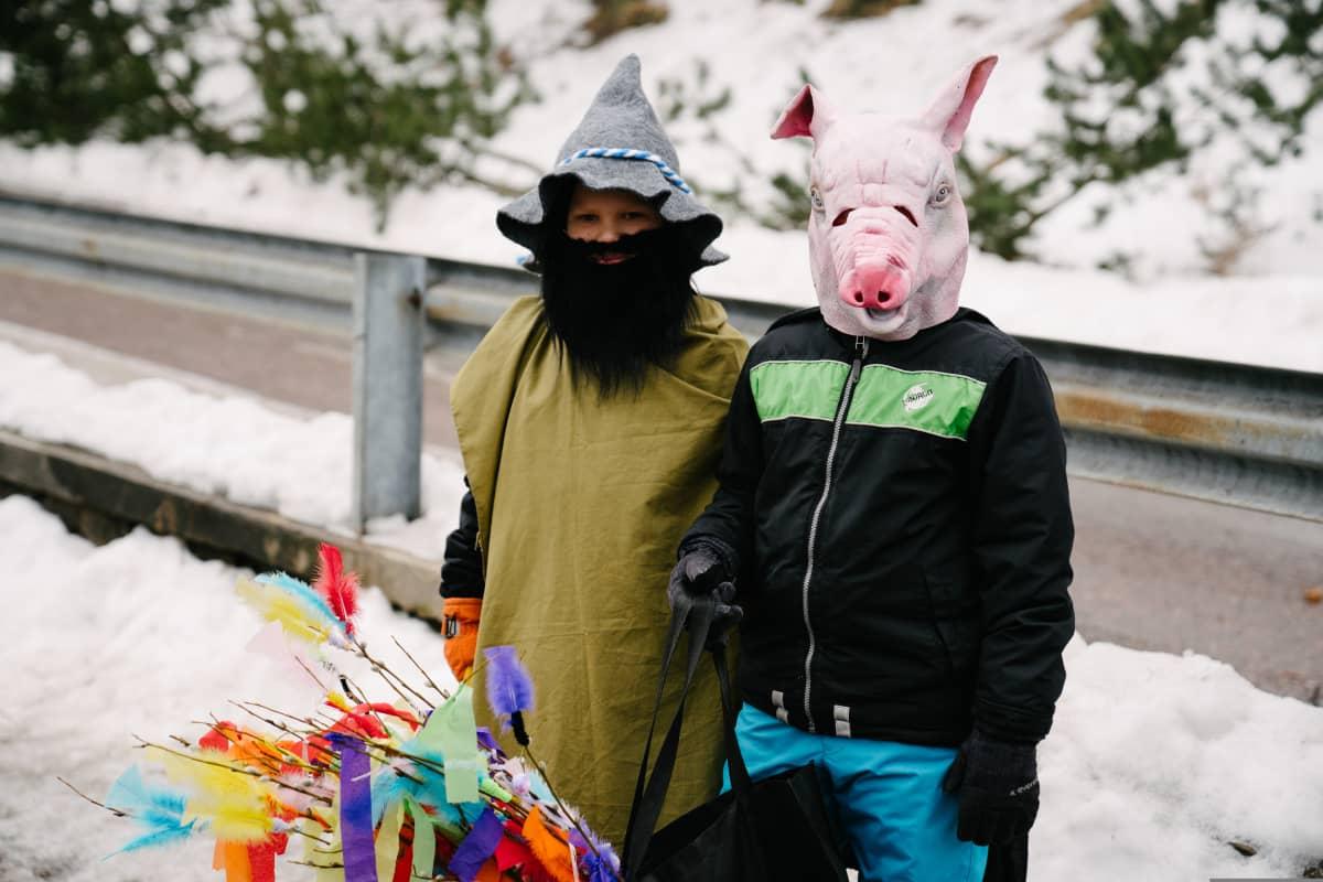 Kaksi poikaa naamiaisasuissa kadulla