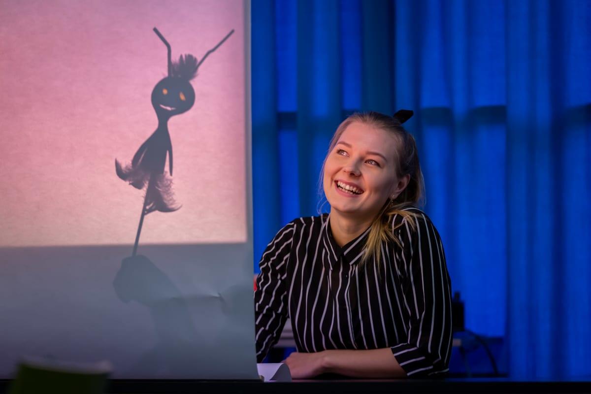 Aalto yliopiston kuvataidekasvatuksen opiskelija Senni Tuomi näyttää, miten varjoteatteri syntyy.