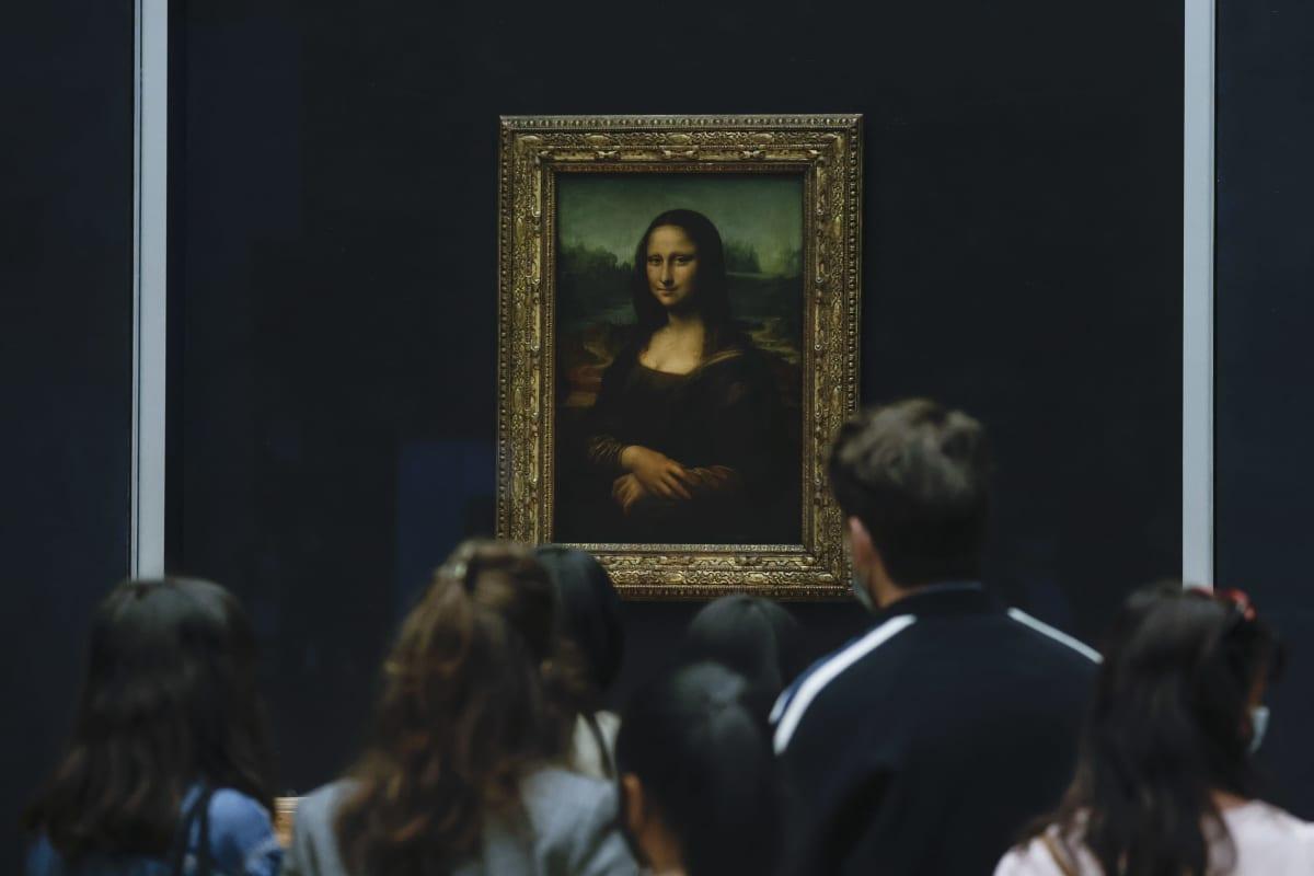 Ihmiset katselevat maalausta seinällä