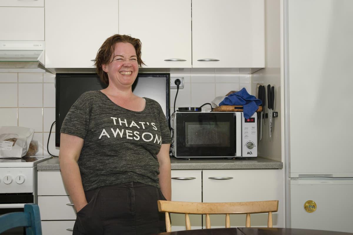 Mimmi Tick nauraa keittiössä kädet hameen taskuissa.