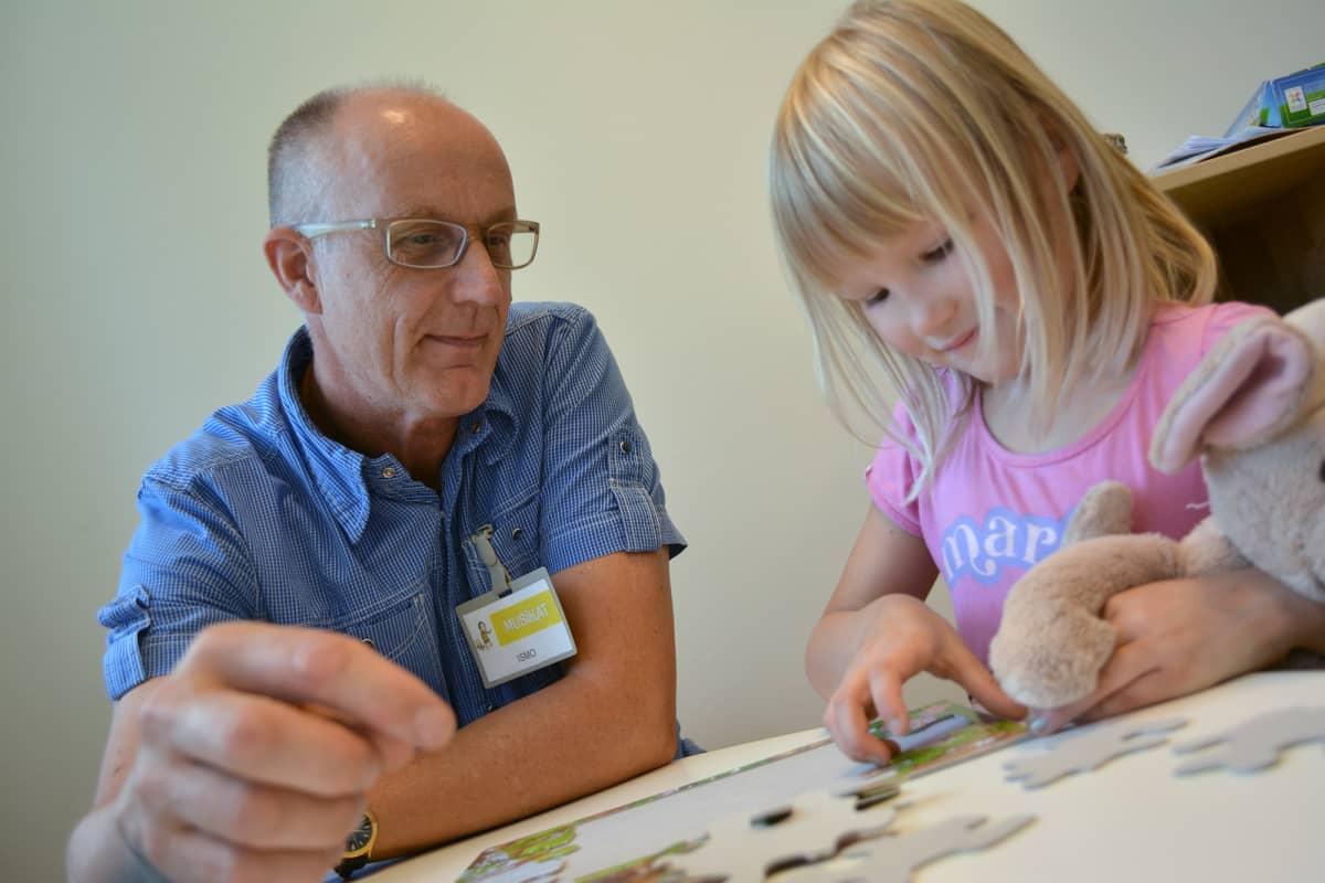 Lastentarhanopettaja Ismo Rautianen opettaa Venla-tyttöä palapelin kokoamisessa.