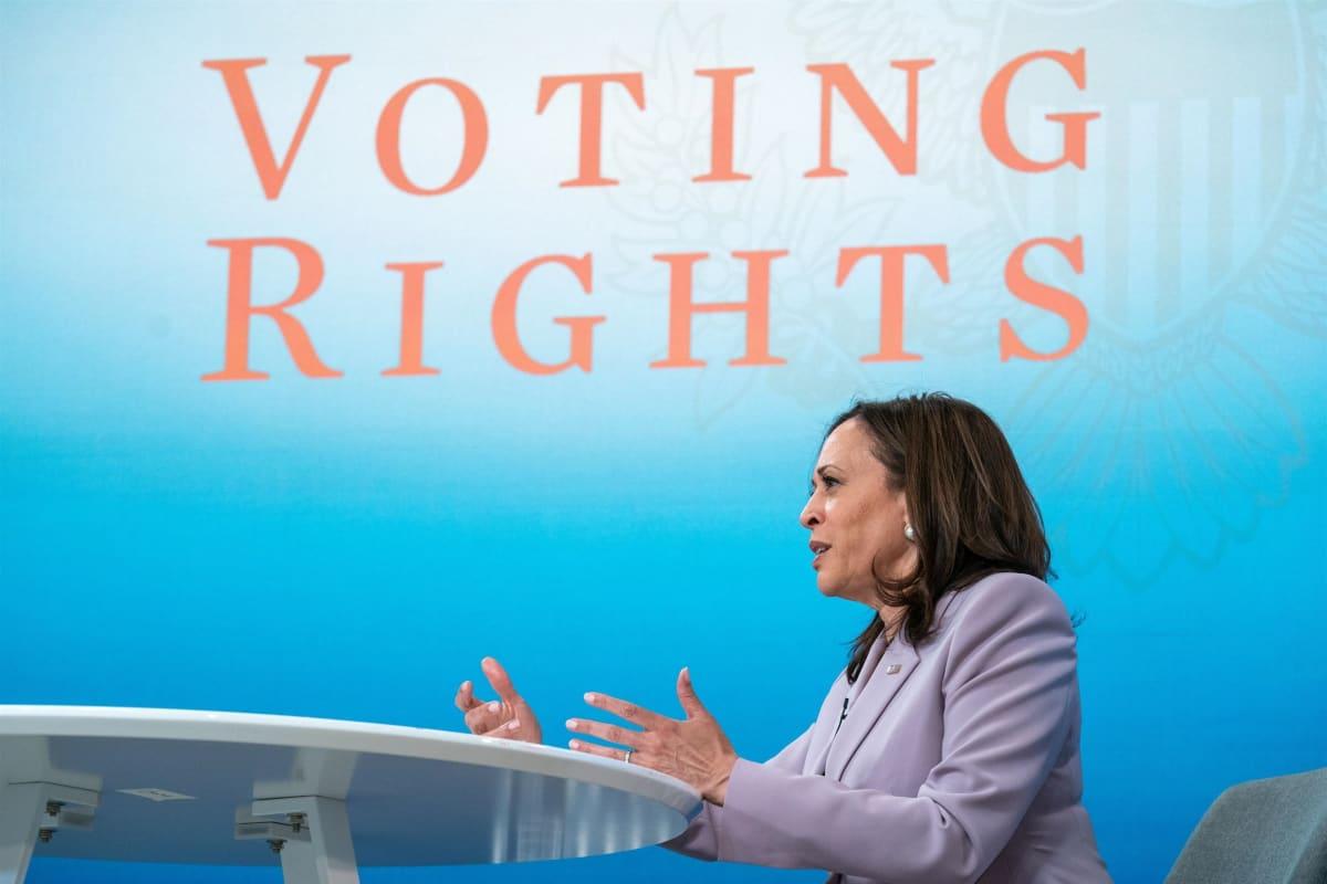 """Kamala Harris puhuu pöydän ääressä. Taustakankaassa lukee """"Voting rights""""."""