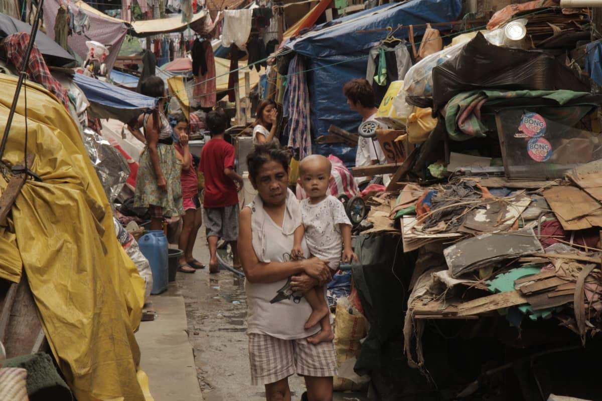 Nainen kantaa lasta ahtaalla kujalla jonka reunalla on hökkeleiltä Manilassa Filippiineillä