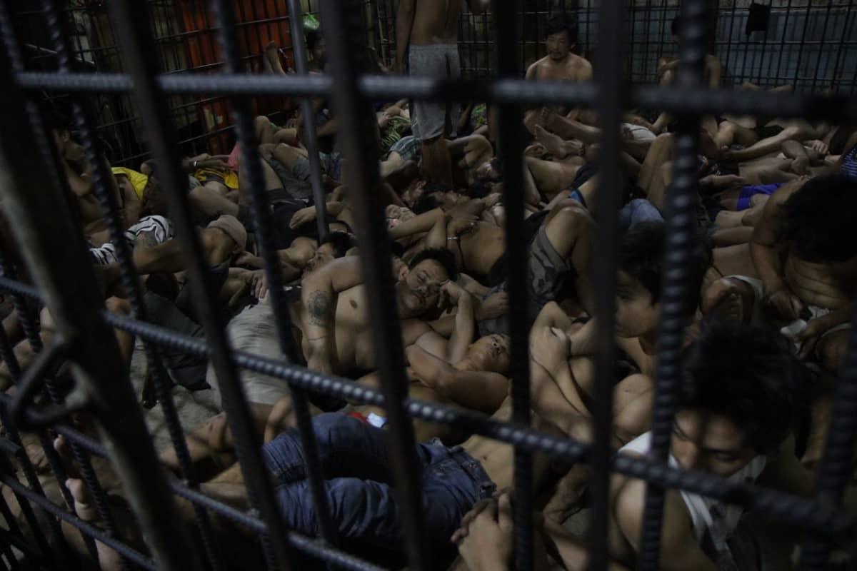 Kaltereiden takana lattialla istuu ja makaa miehiä ilman paitaa. He ovat vieri vieressä poliisisellissä Manilassa.