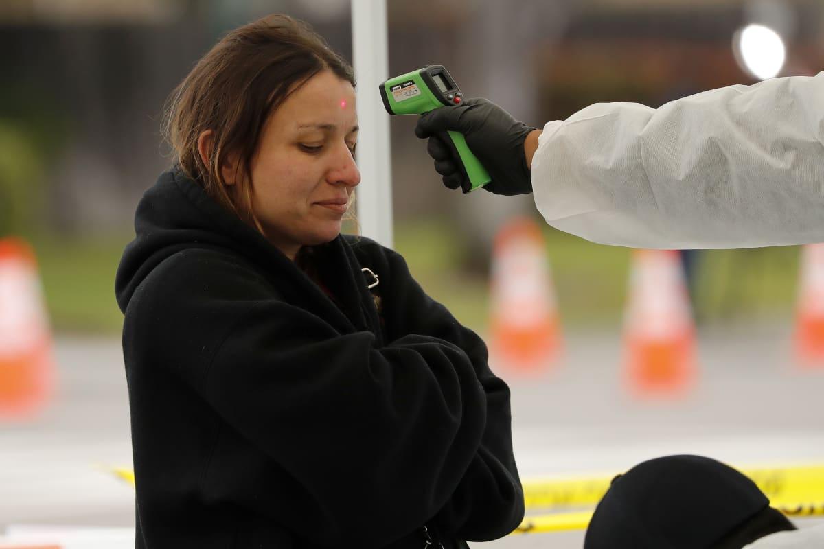 Naiselta mitattiin maanantaina ruumiinlämpöä koronatestipaikalla Haywardissa, Kaliforniassa.