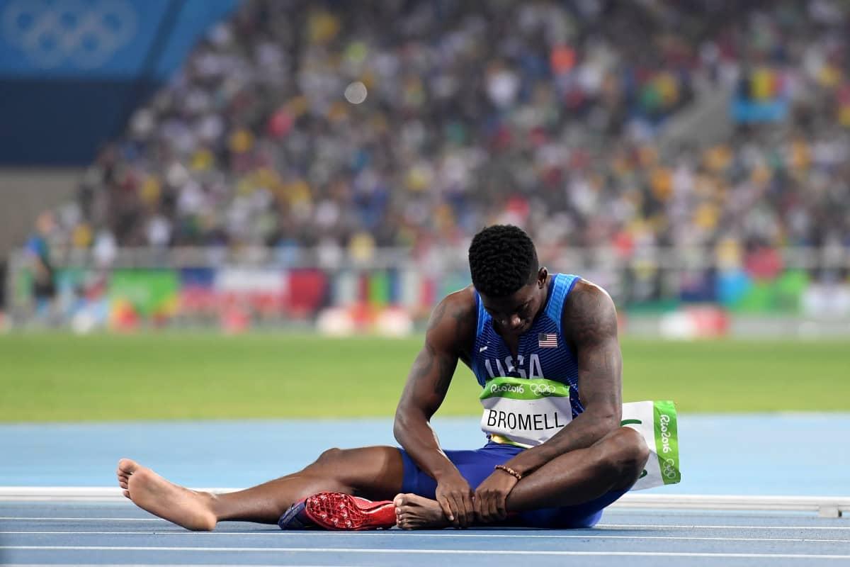 Pikajuoksija Trayvon Bromell istuu juoksuradalla ja pitelee vasenta nilkkaansa.