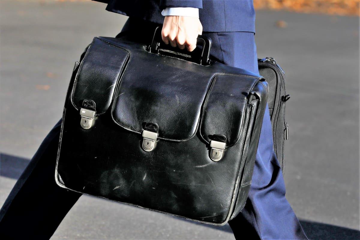 Siniasuinen mies kantaa isoa mustaa nahkasalkkua.