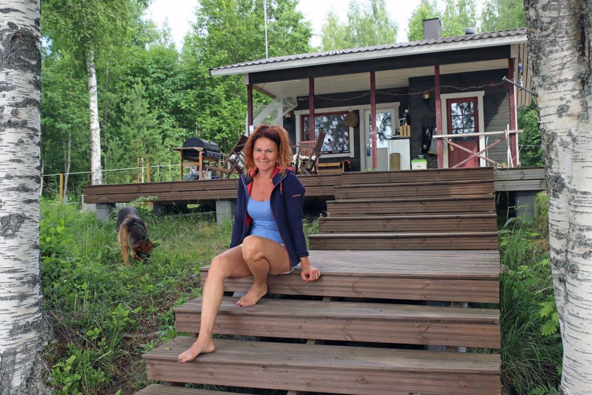 Melina Holmberg istuu mökkinsä kuistilla.
