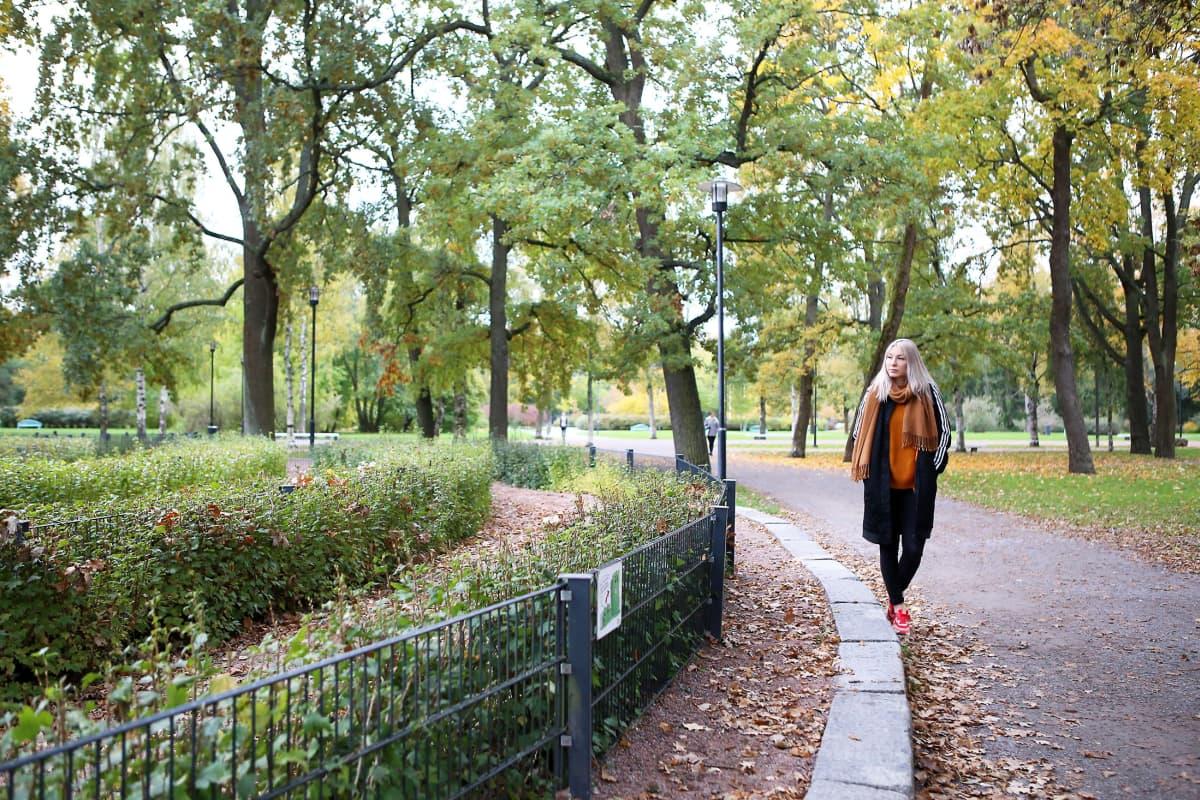 Salla-Maarit Karpio kävelee puistossa syksyllä.