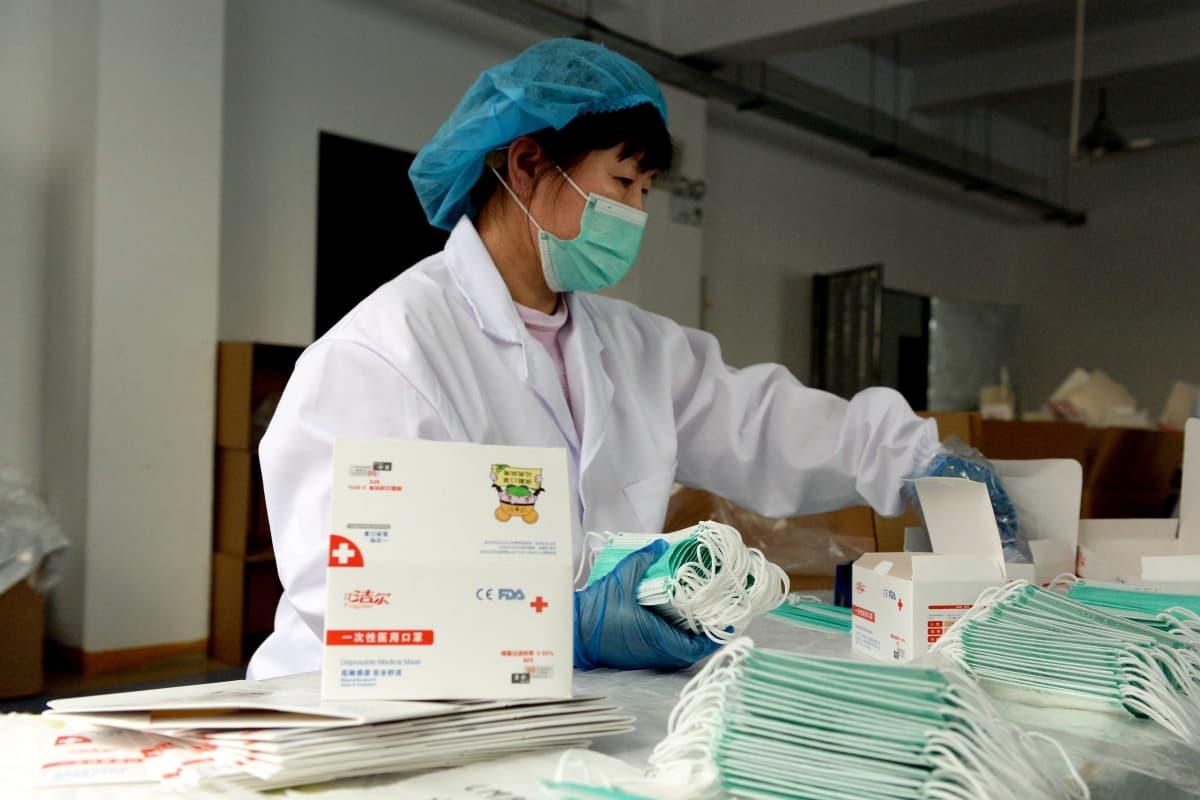Kiinalainen työläinen pakkaa vaaleansinisiä kasvomaskeja. Hänellä on itselläänkin kasvosuojain ja muut suojavarusteet yllään.