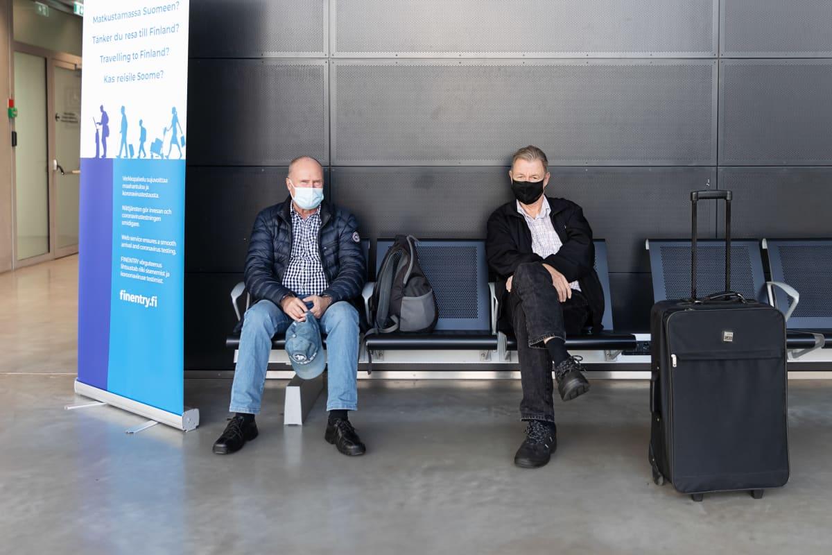 Jukka Pennanen ja Kari Pelkonen istuvat penkillä lipunmyyntihallissa ja odottelevat laivan lähtöä.