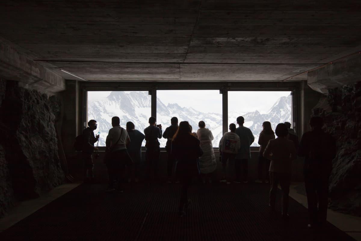 Ihmisiä ikkunan siluettia vasten.