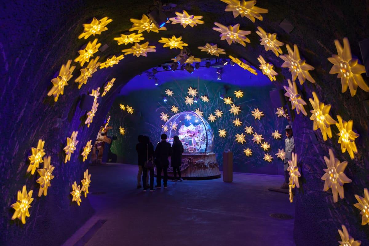 Tunneli, jossa on valaistuja kukkia katossa.