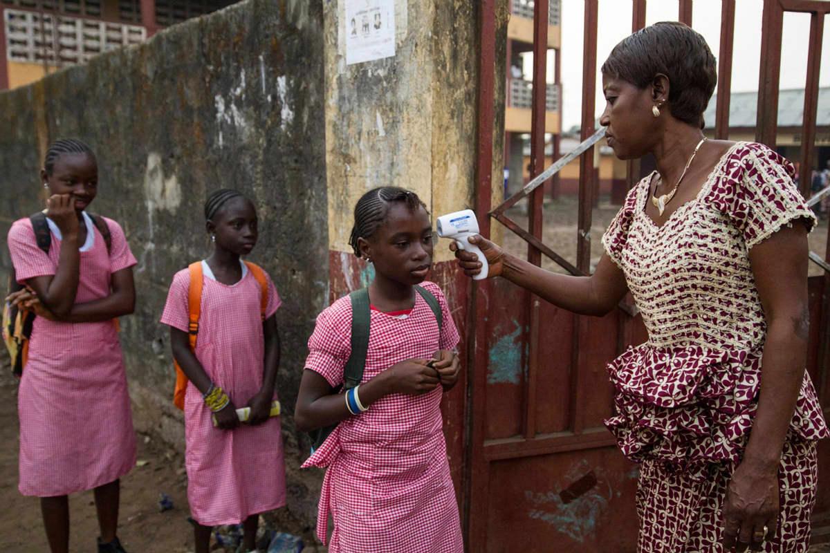 Lapsilta mitattiin lämpö koulun portilla tammikuussa 2015, kun koulut avautuivat pitkän sulun jälkeen. Kuva on otettu Guinean pääkaupungissa Conakryssa edellisen ebolaepidemian aikana.