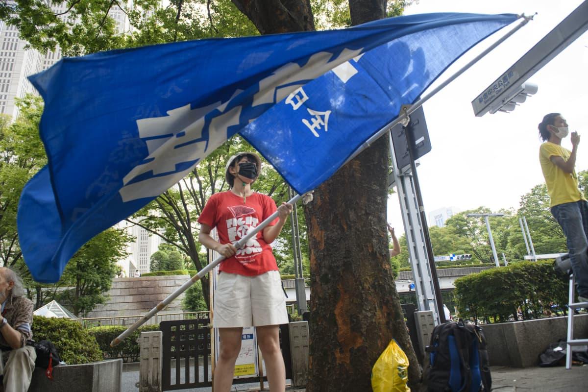 Opiskelija Hiro Yajima heilutti mielenosoituksessa lippua.