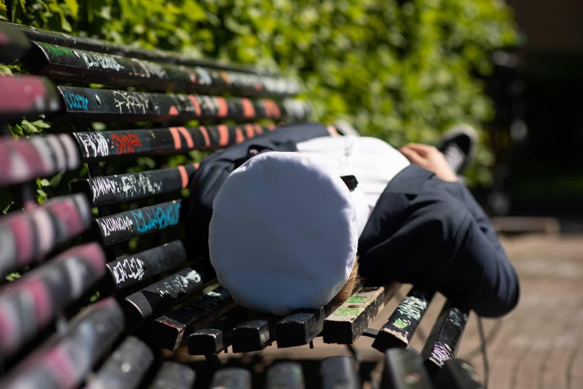 Ylioppilas makaa puiston penkillä.