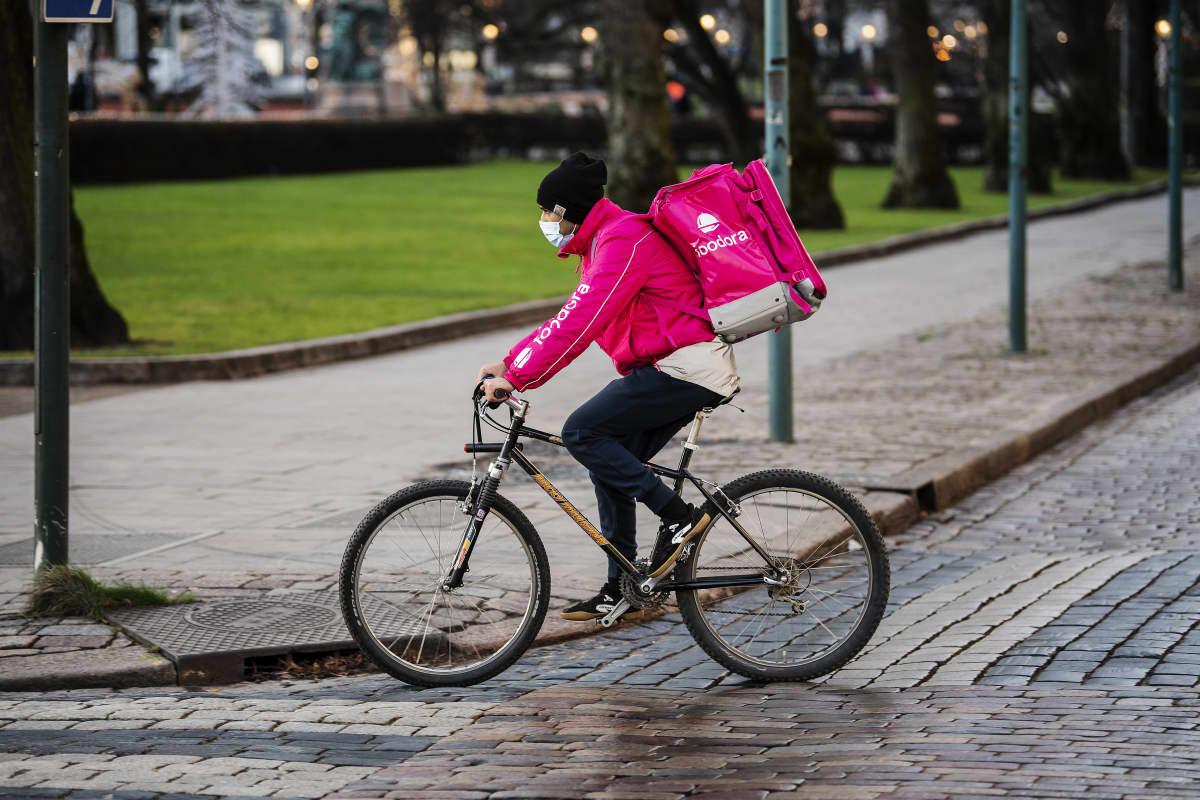 Foodoran ruokalähetti polki Helsingin keskustassa kasvomaski kasvoillaan joulukuussa 2020.