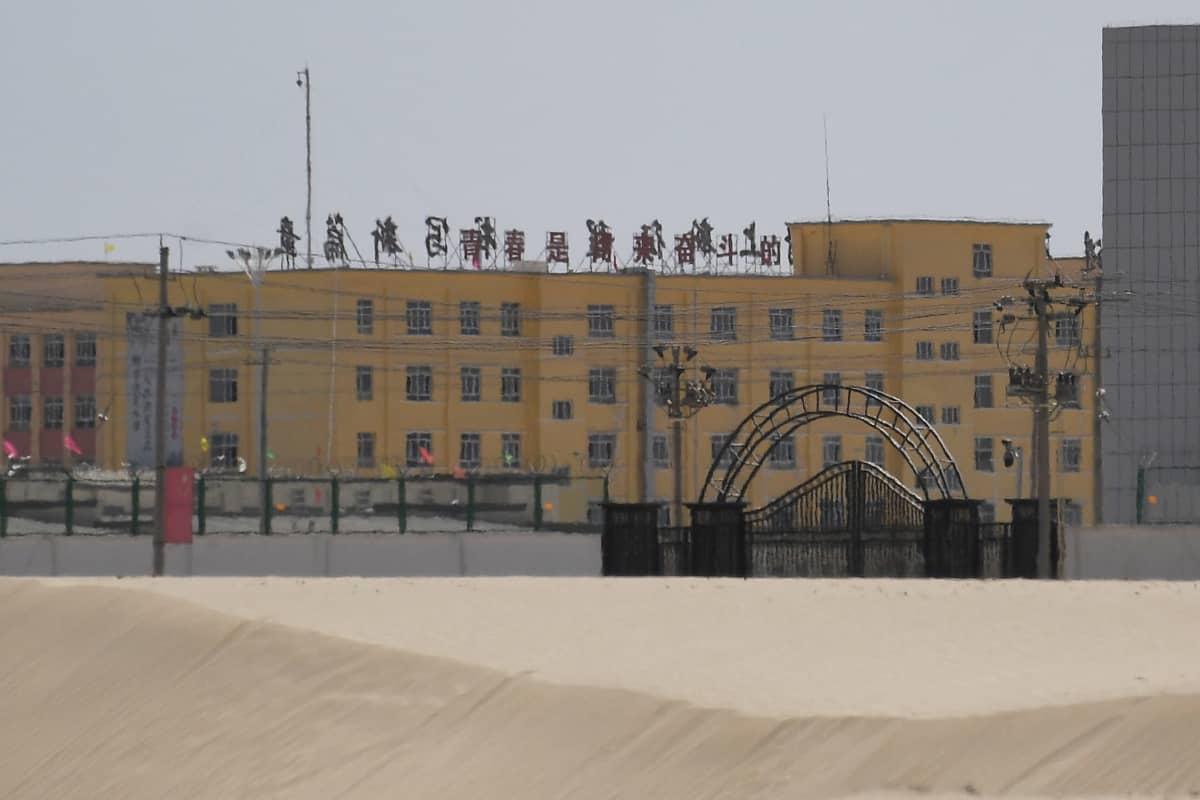 Kiinan lippuja suljetun portin ja korkealla aidalla aidatun alueen edustulla.