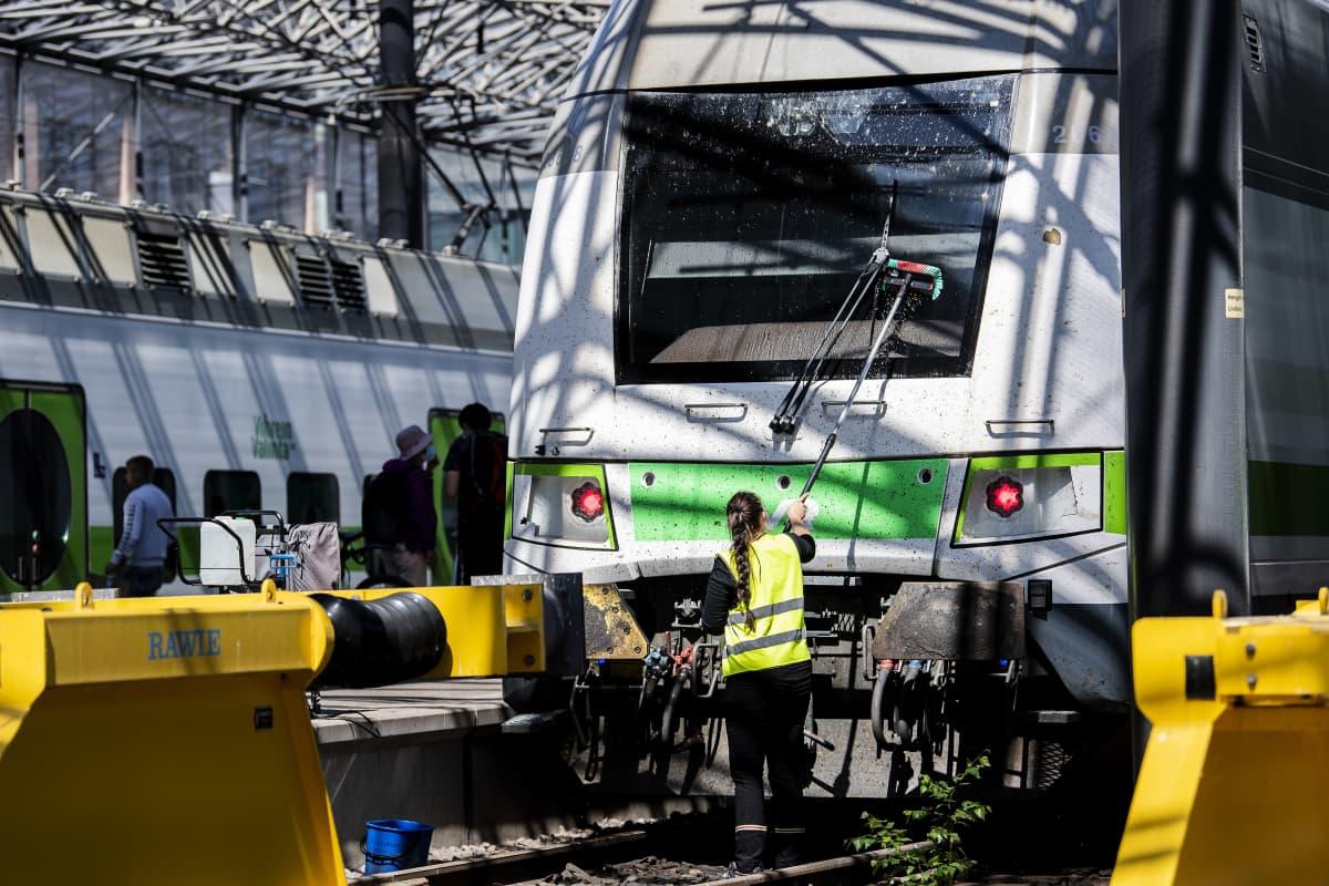 Työntekijä pesi veturin etulasia Helsingin päärautatieasemalla kesäkuussa.
