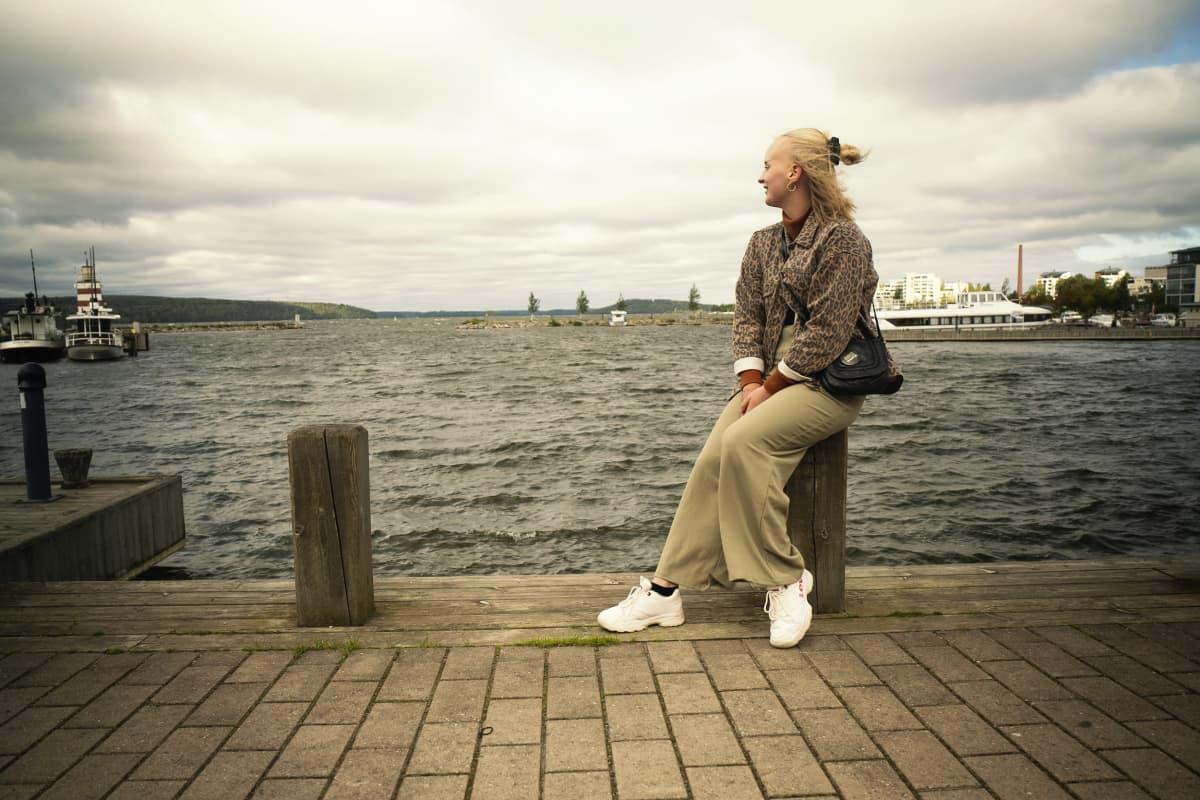 Jasmin Tuomi istuu satamassa olevan puupalkin päällä. Jasmin katsoo kohti aaltoilevaa järveä.