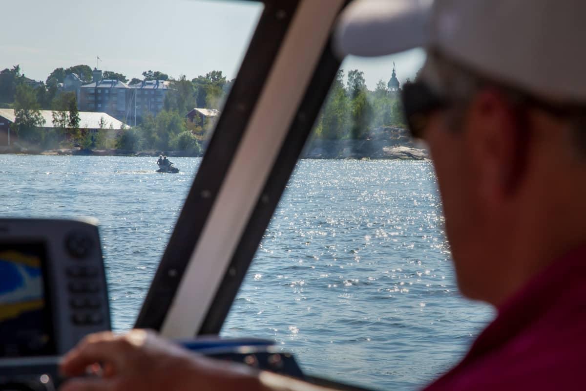 Mies seuraa veneestä, kun merellä kauempana kulkee vesiskootteri.