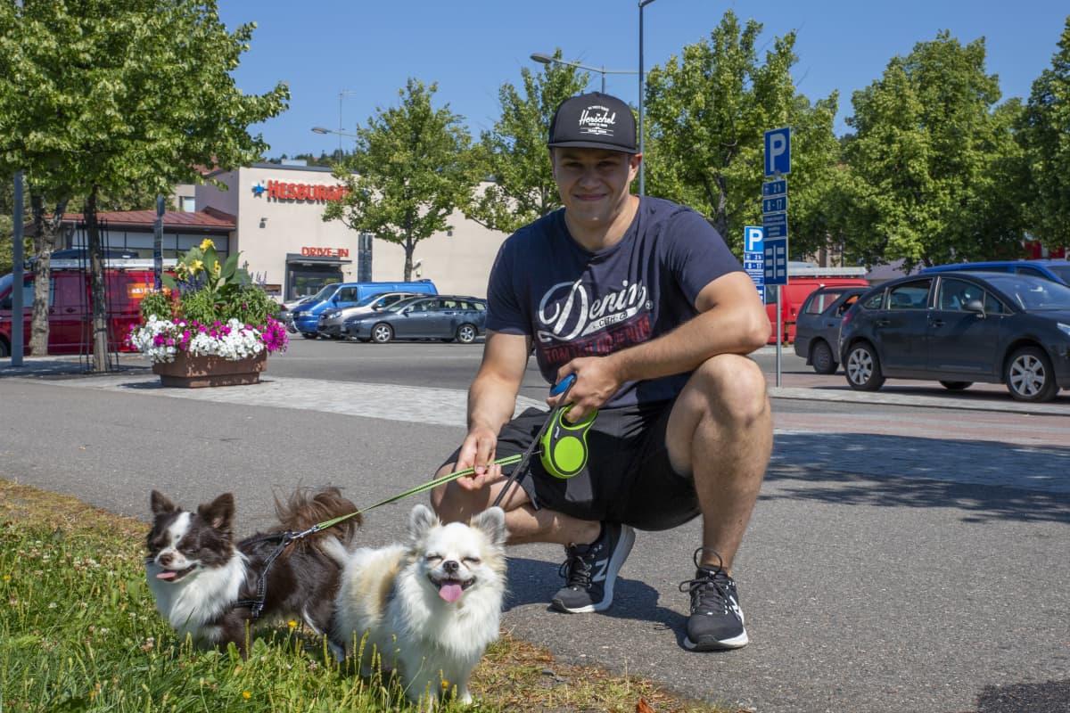 Jesse Liimatainen kyykyssä kahden pienen koiransa kanssa.