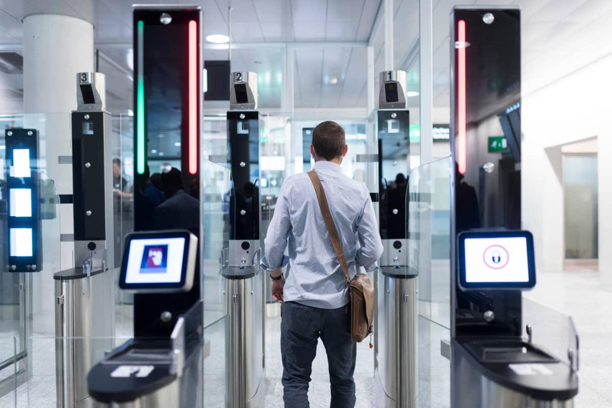 Mies menee automaattisen turvaportin läpi